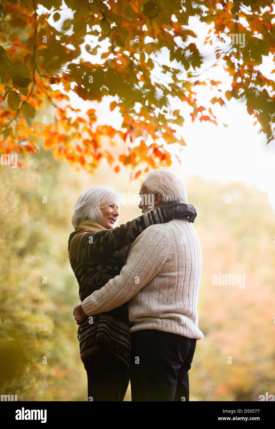 Older couple hugging in park - Stock Image
