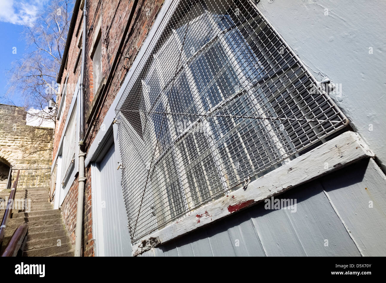 Old building with a wire mesh guard to protect the window Stock Photo