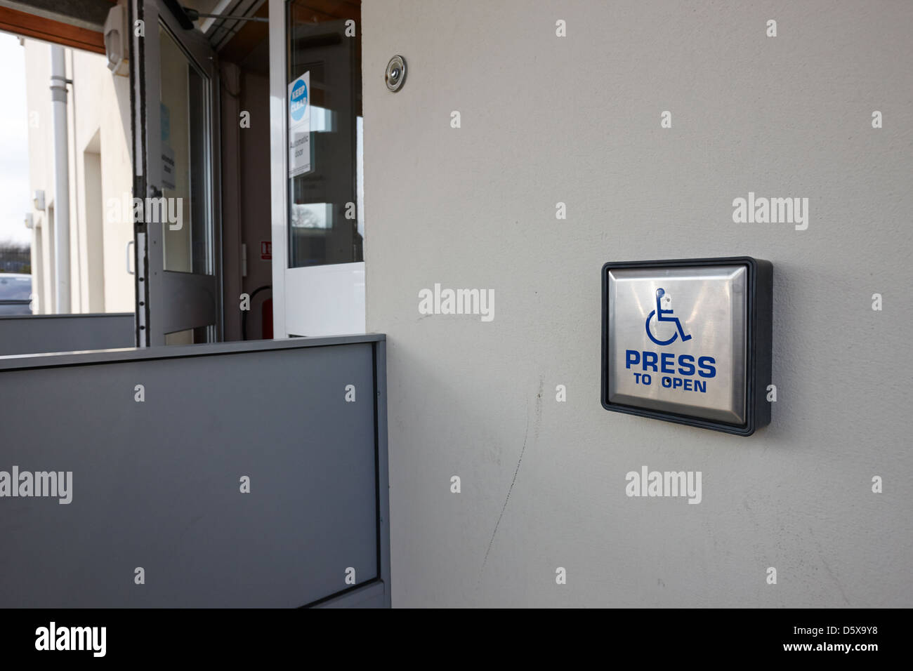 press to open disabled automatic door access to a public building northern ireland uk - Stock Image