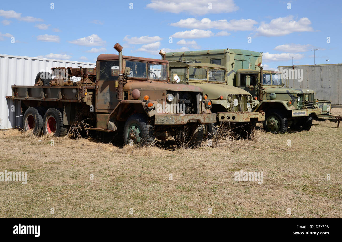 Three old army vehicles parked in a grass field. - Stock Image