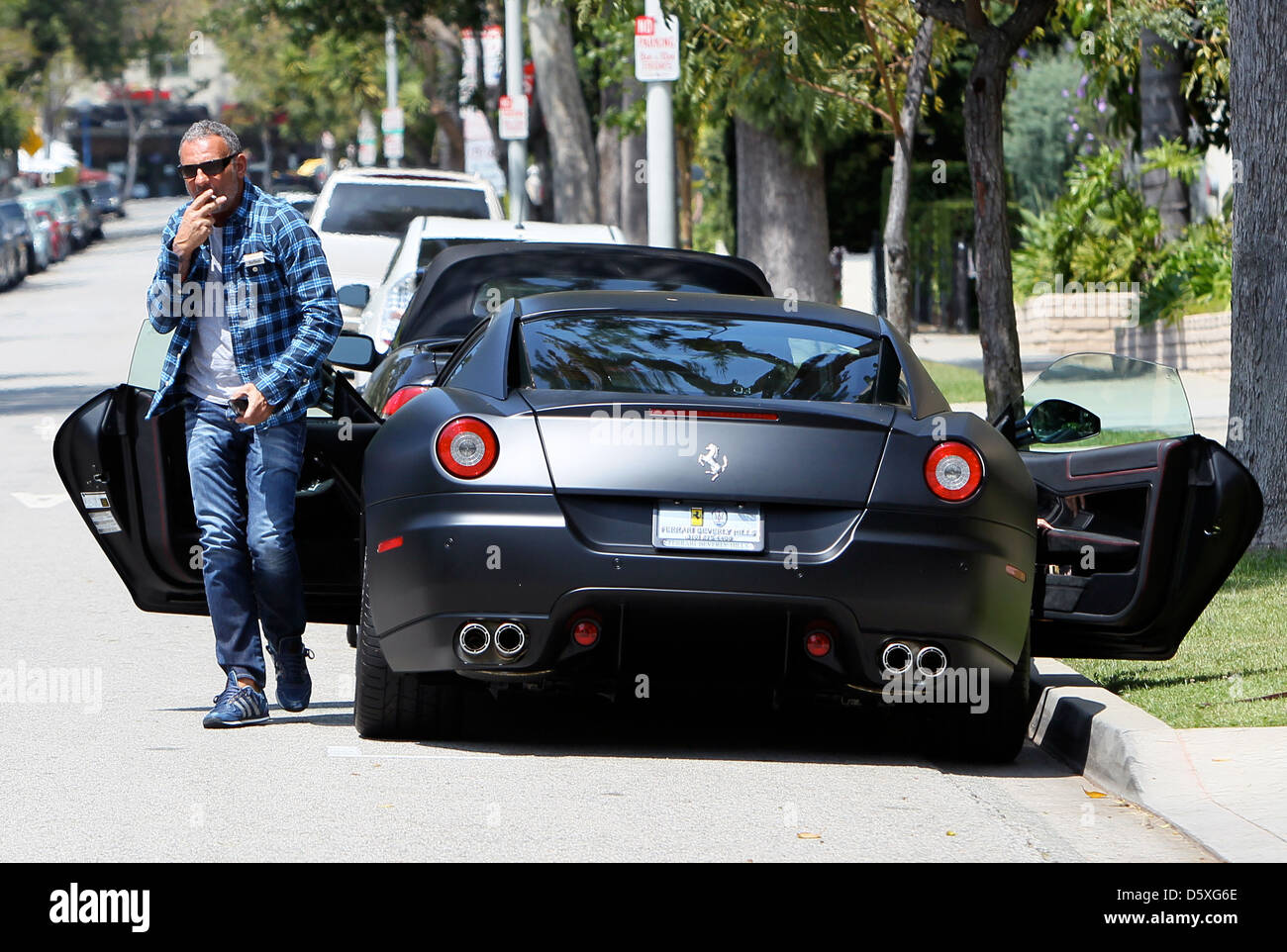 christian audigier and his girlfriend drive his matte black ferrari