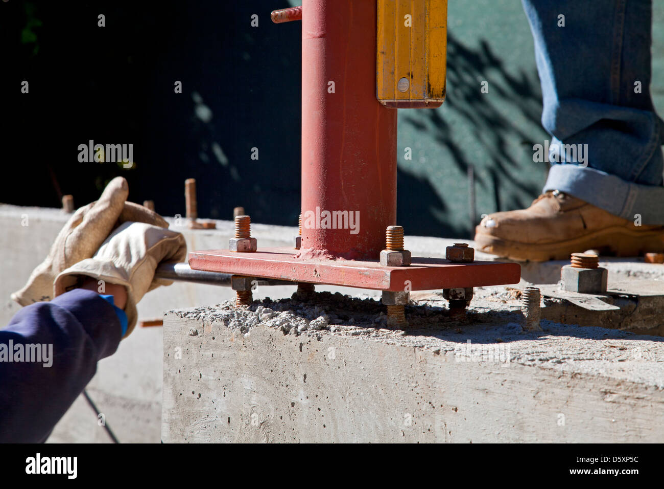Vertical steel beam is leveled using four bolts spaced from the concrete foundation. Los Angles, California, USA - Stock Image