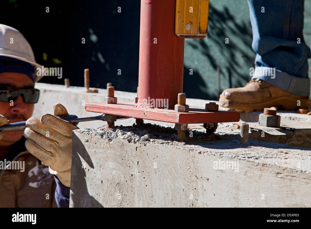 Vertical steel beams are leveled off of foundation. - Stock Image
