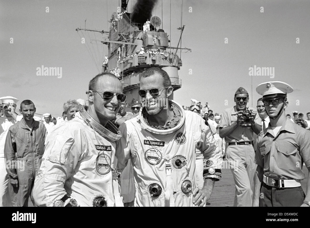 U.S. astronauts L. Gordon Cooper Jr. (right) and Charles Conrad Jr. walk across the deck of the recovery aircraft Stock Photo