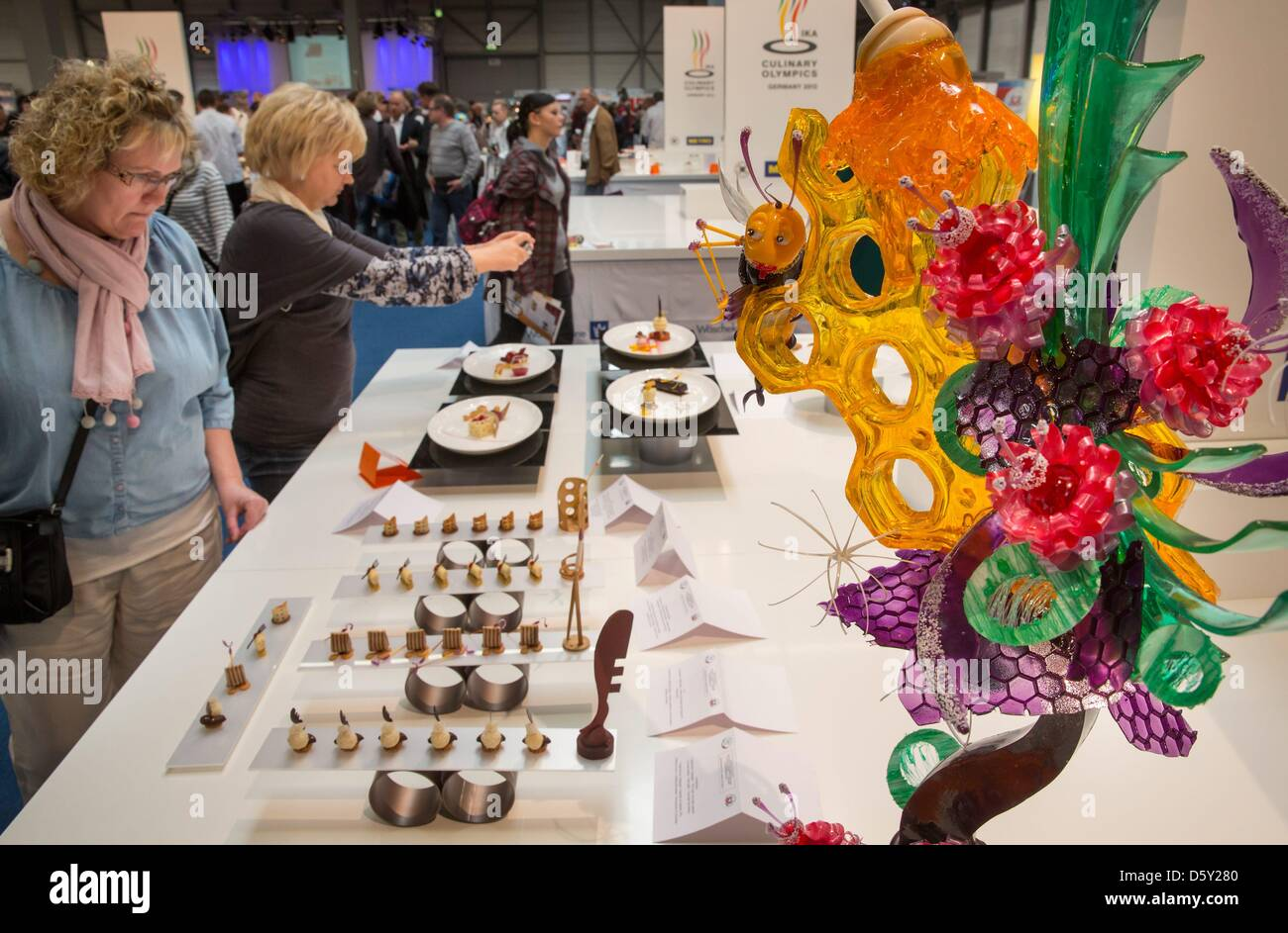 Visitors view showpieces of the different teams competing in the 'Cooking Olympics' at the International - Stock Image