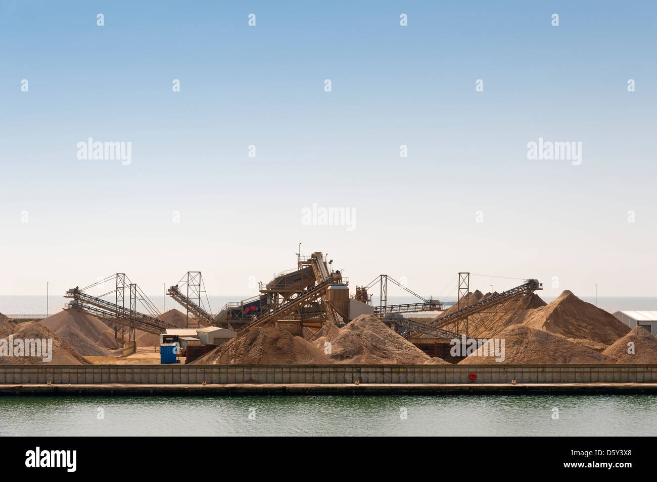 Huge piles of aggregates at an industrial processing plant in Shoreham Harbour - Shoreham-by-Sea, East Sussex, UK - Stock Image