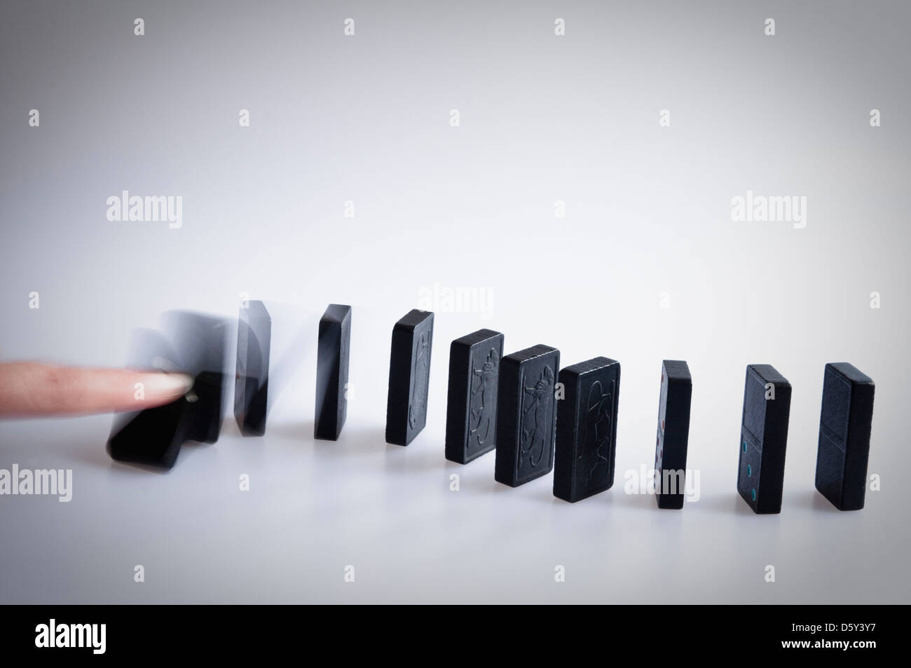 Dominoes falling - finger pushing over the first domino and showing motion blur as it falls. - Stock Image