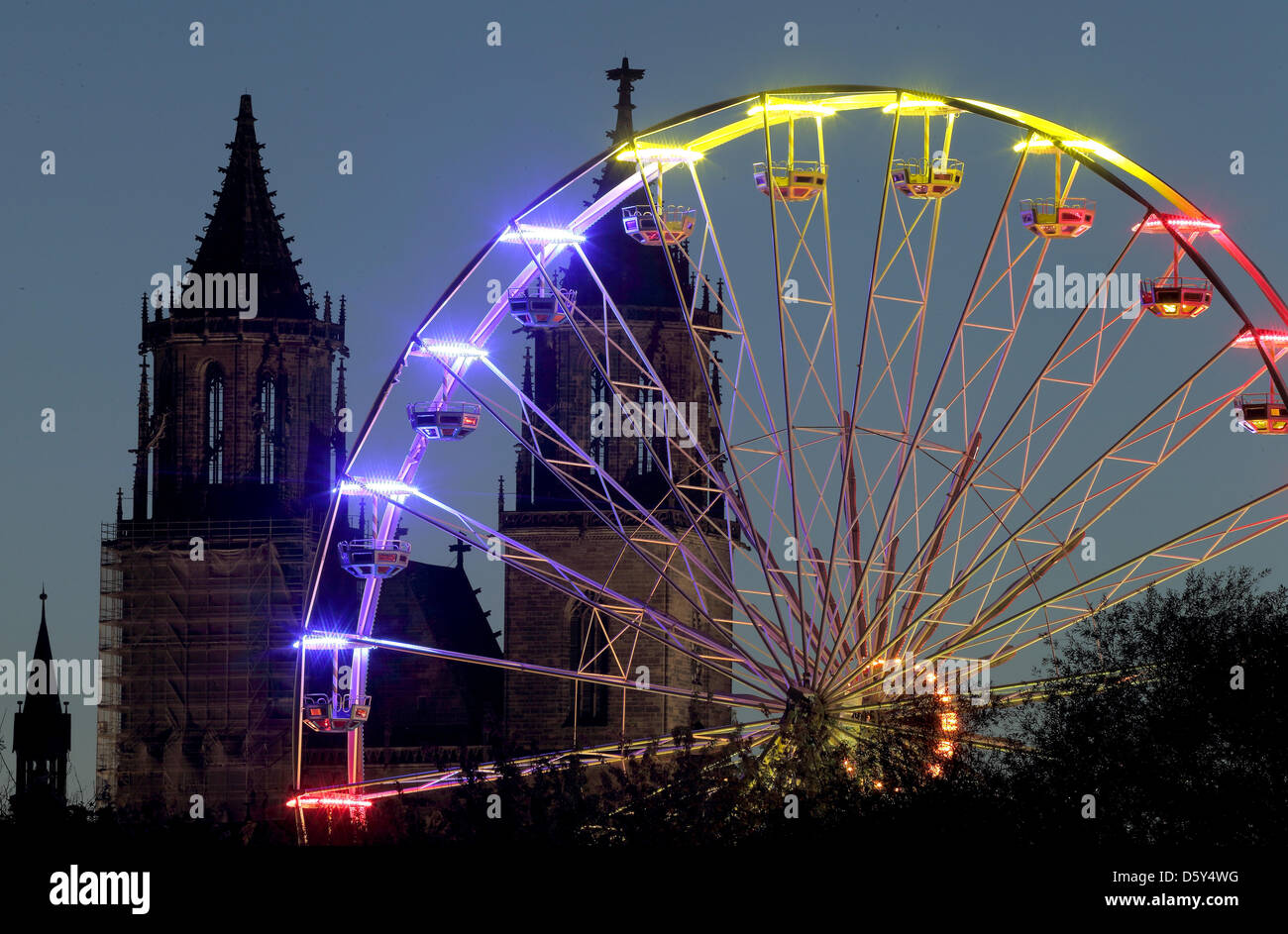 A ferris wheel, that is illuminated with colorfull lights, is visible in front of the Cathedral 'Saint Katharina Stock Photo