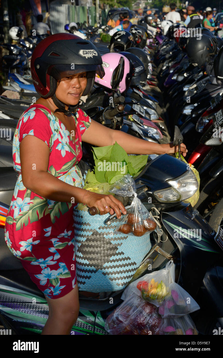 Indonesia, Bali, woman on a motobike leaving the parking at the market in Ubud - Stock Image