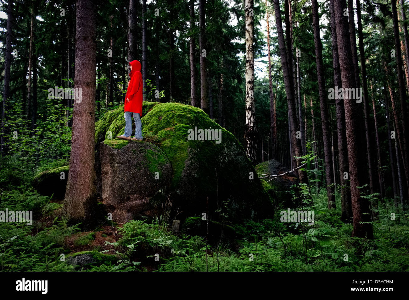 Young woman wearing a Red riding Hood in the middle of a forest. - Stock Image