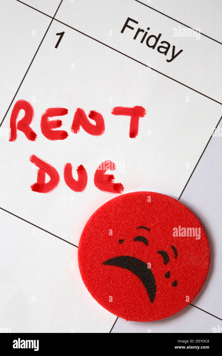 1st of the month and rent due written in red with red sticker crying face on calendar - Stock Image