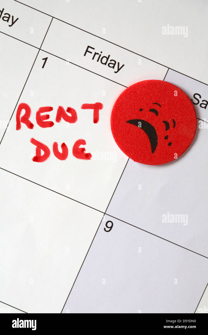 1st of the month and rent due with red sticker crying face on calendar - Stock Image