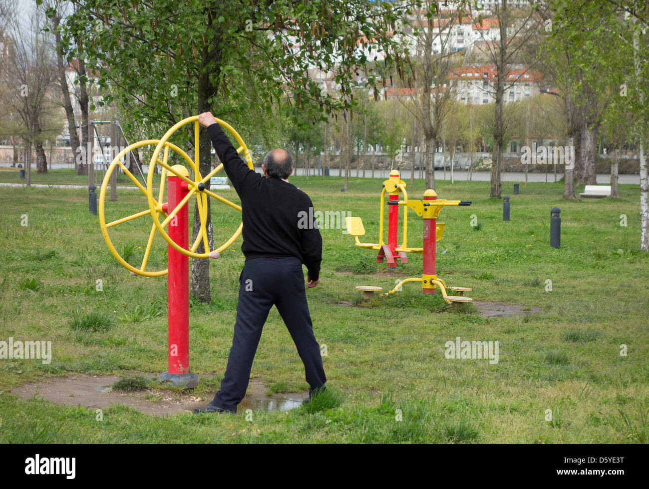 Person working out in an outdoors public fitness park - Stock Image