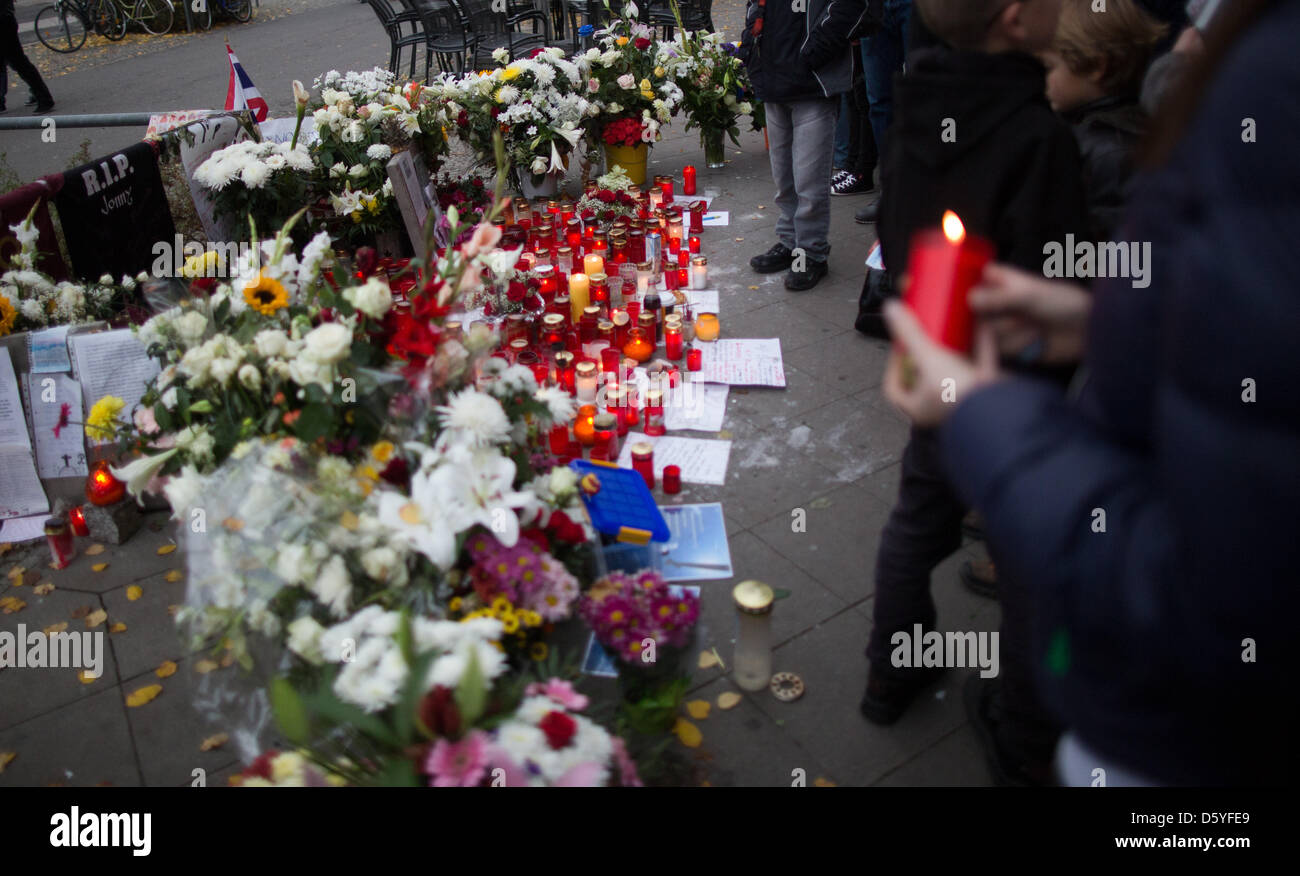 Pedestrians stand at the spot where a young man, who was so brutally beaten and kicked that he died one day later - Stock Image