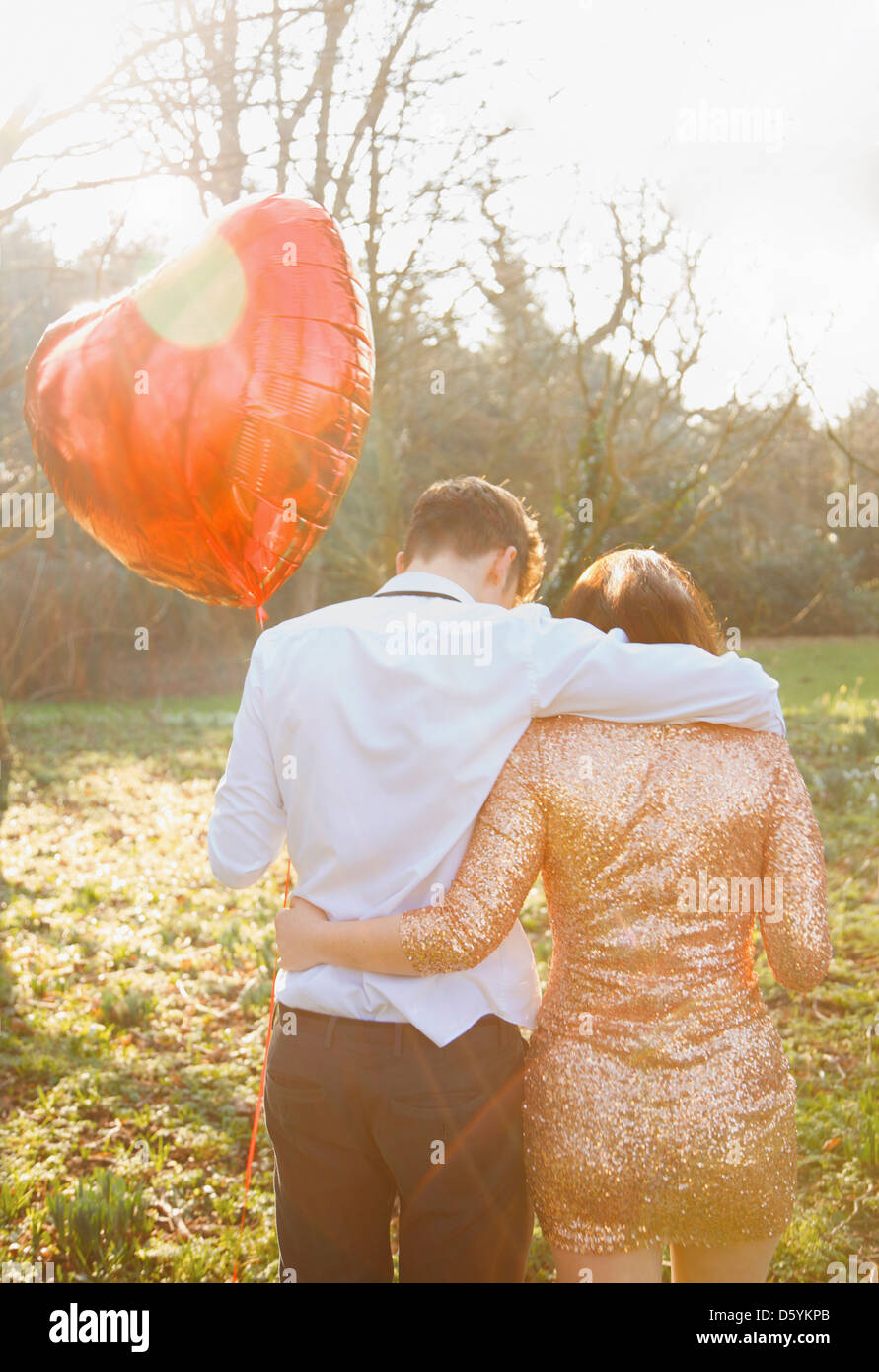 Couple in Park Holding Heart Shaped Balloon, Back View Stock Photo