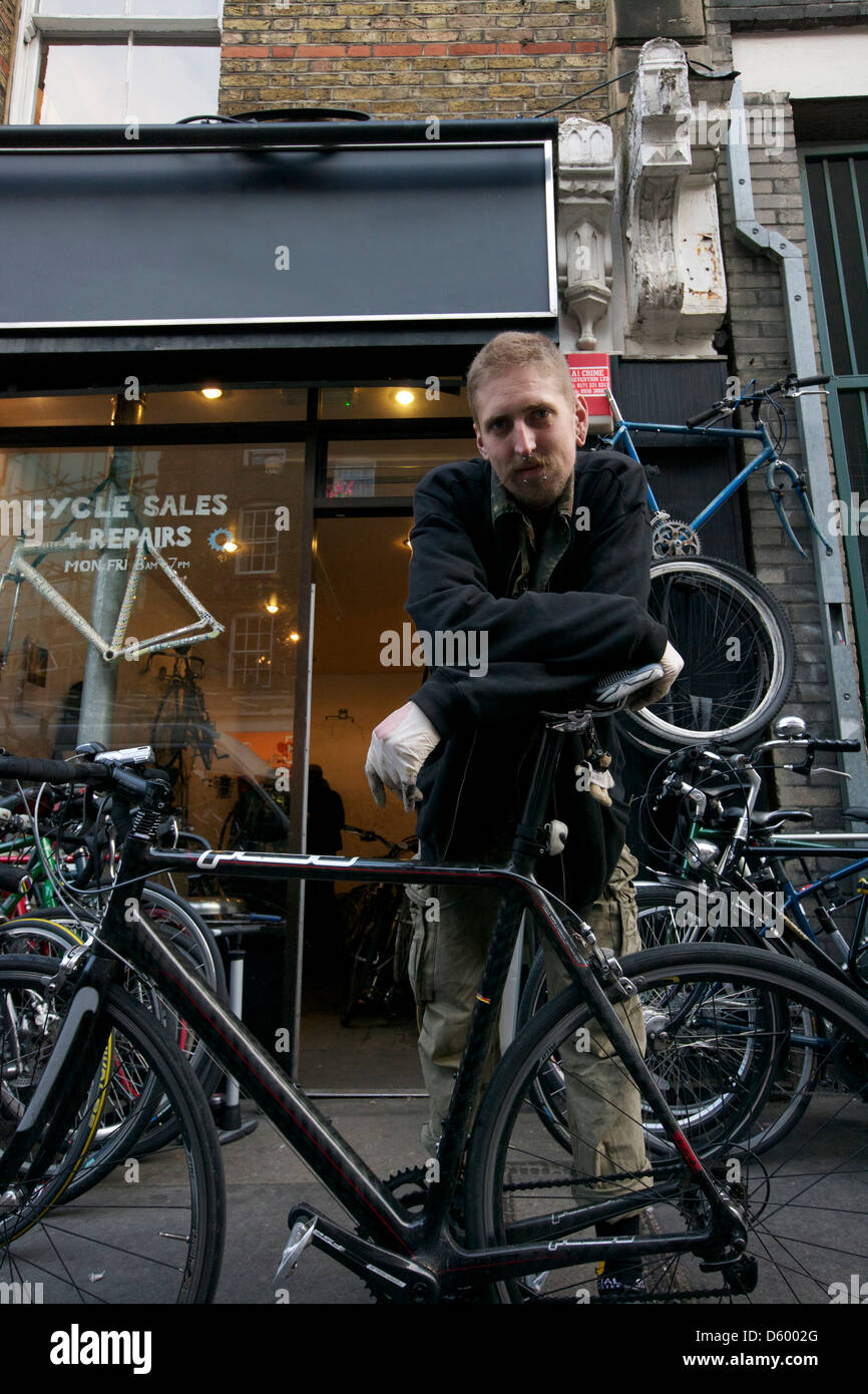 Portrait of mid dult man standing outside cycle shop - Stock Image