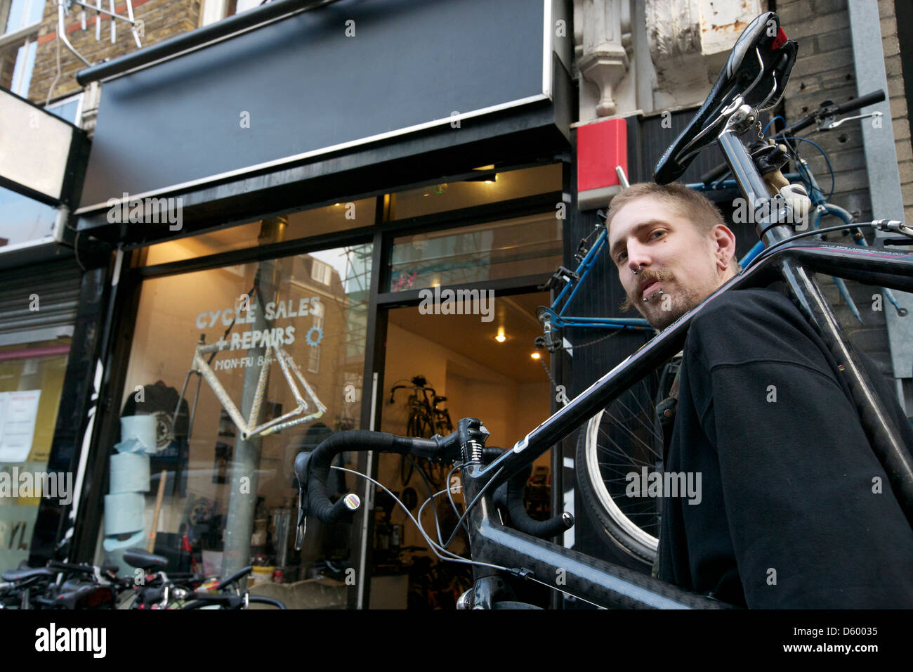 Portrait of  mid dult man carrying bicycle shoulder - Stock Image