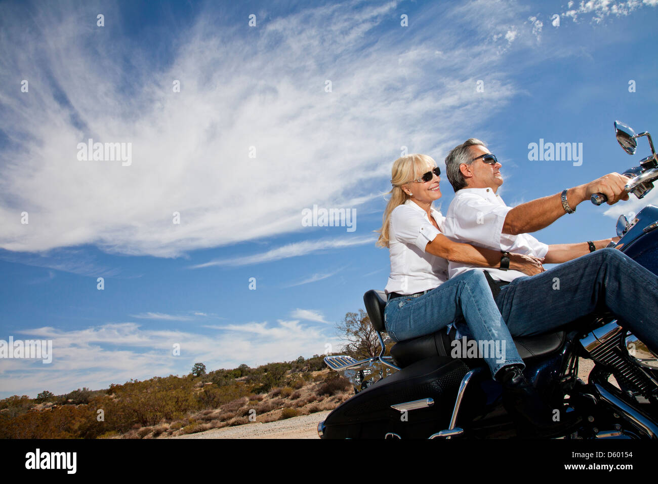 Senior couple riding motorcycle desert road - Stock Image