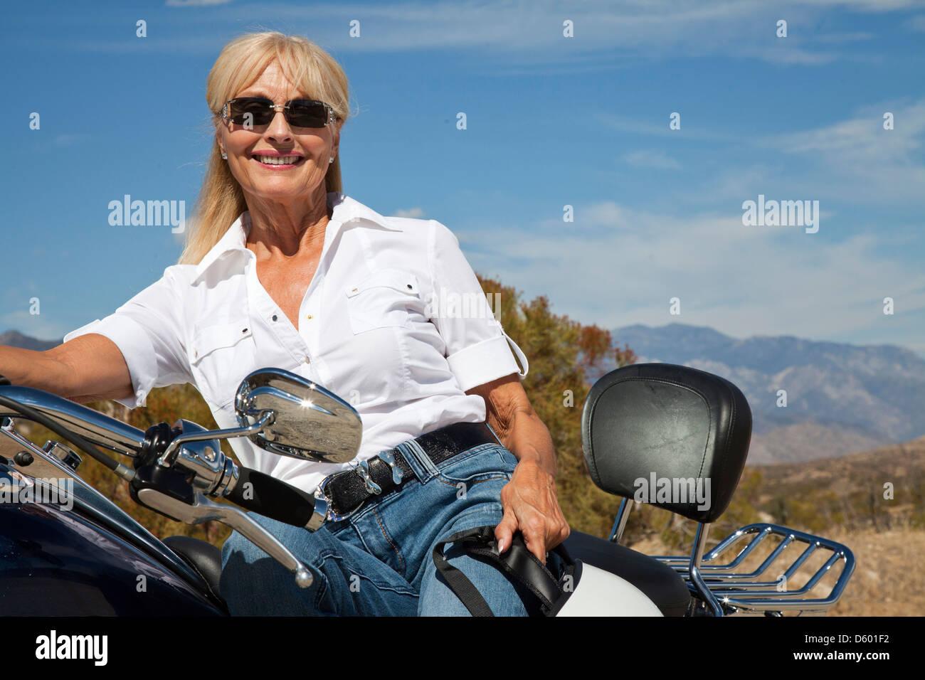 Senior woman sitting motorcycle desert road - Stock Image