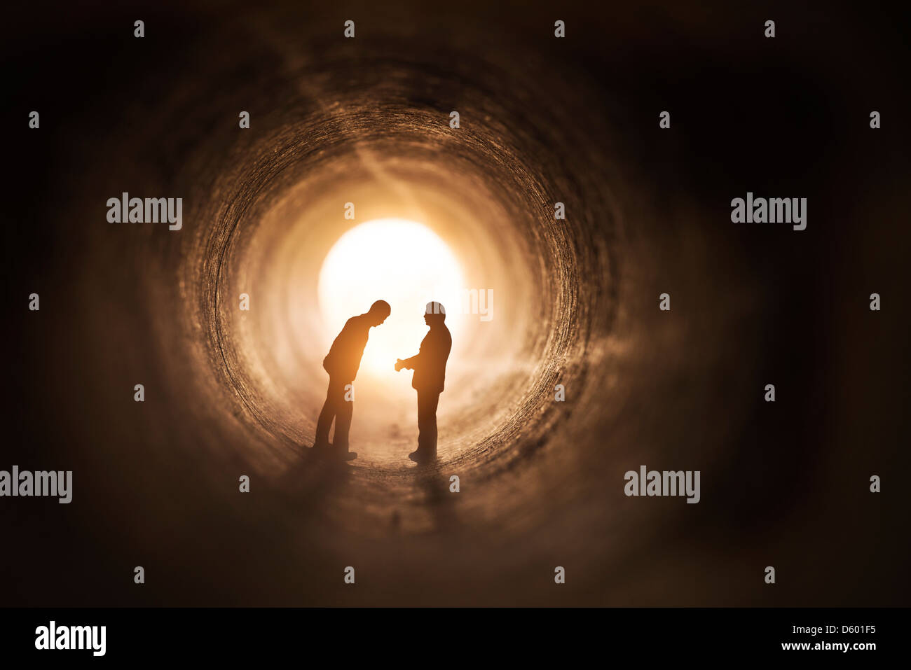 Two businessmen talk within a tunnel. - Stock Image