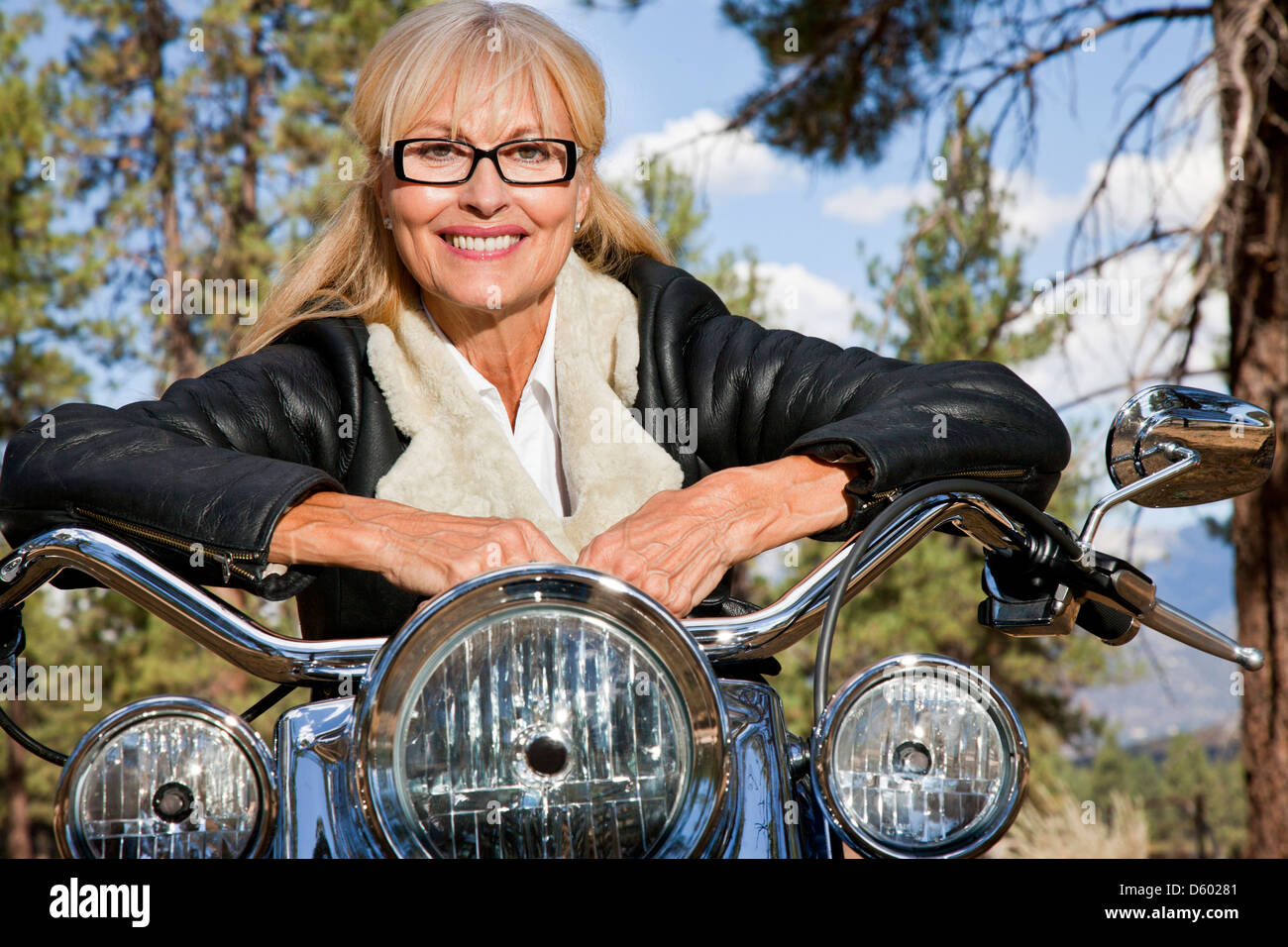 Senior woman leaning motorbike handlebars - Stock Image