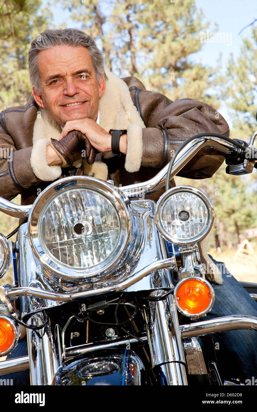 Senior man leaning motorcycle handlebars - Stock Image