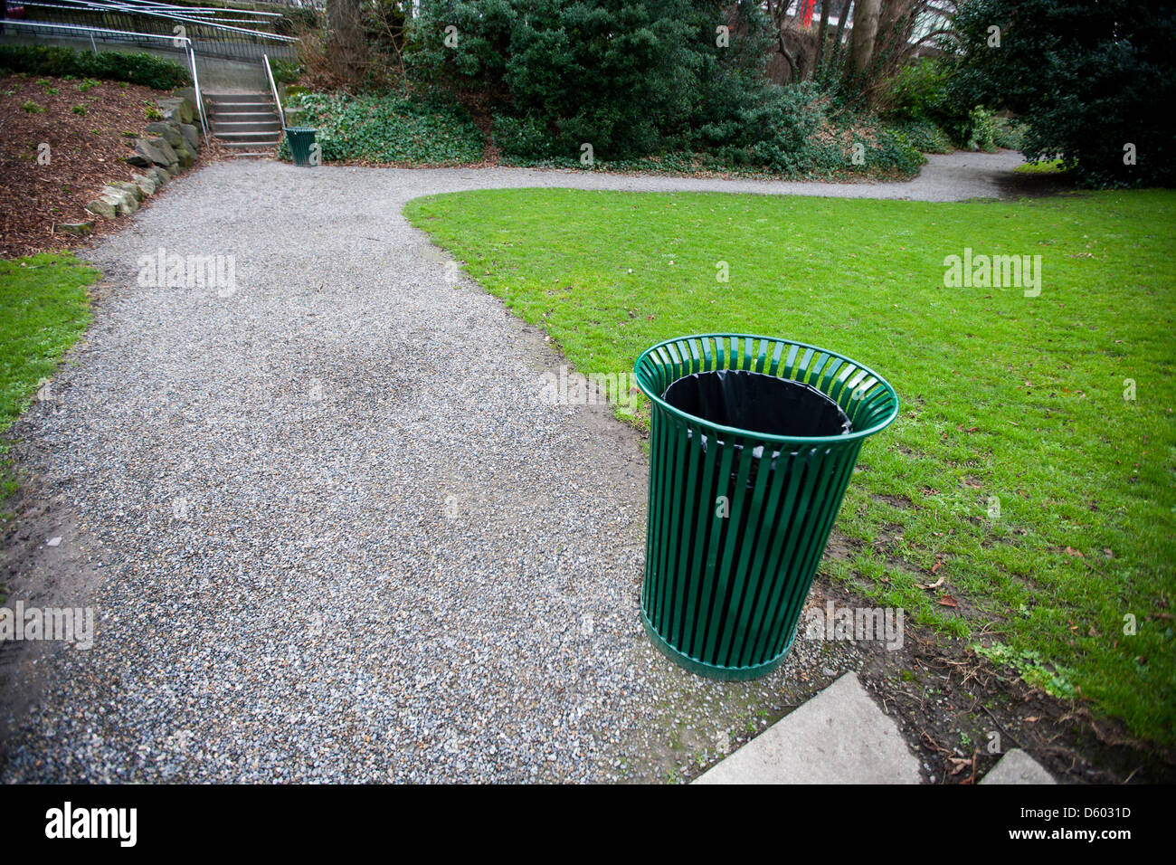 Wide ngle view of trash can by  path in  park Stock Photo