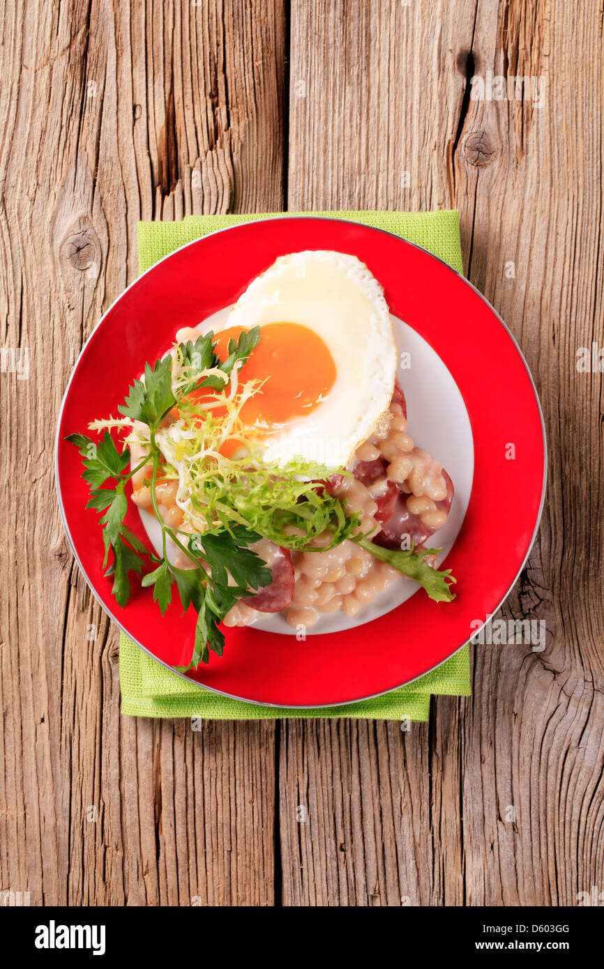 White beans with sausage and fried egg - Stock Image