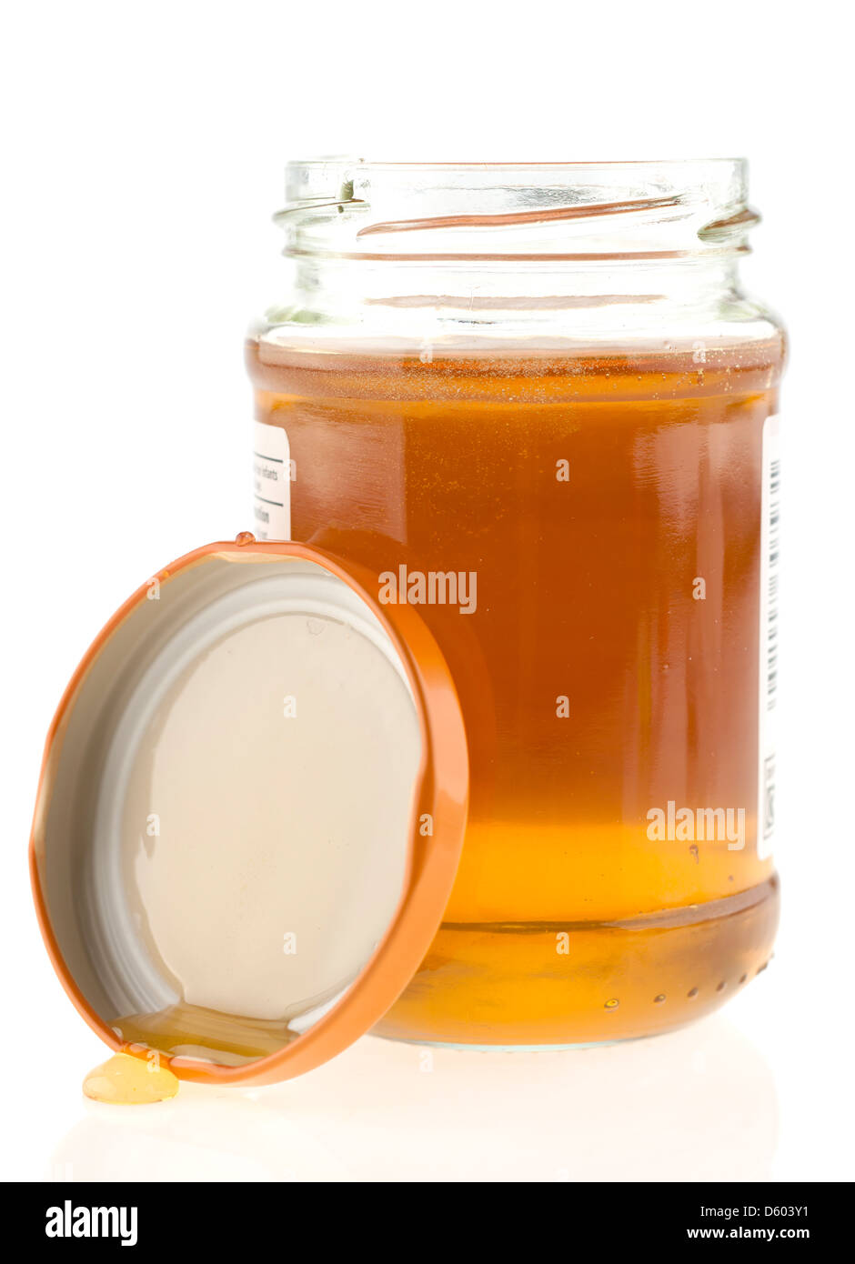 Jar of runny honey with the top removed - Stock Image