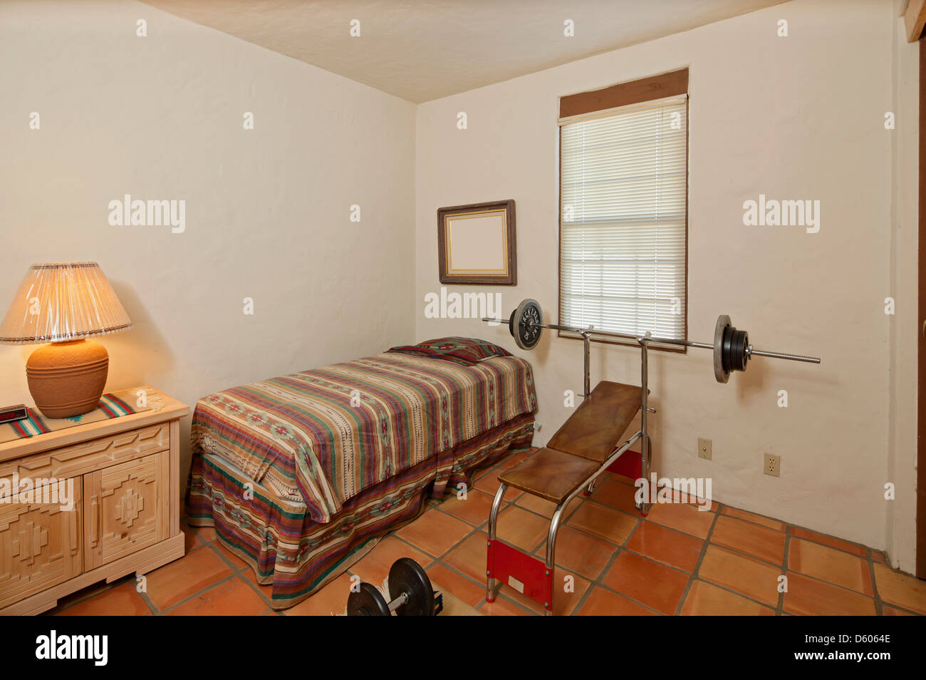 Small single bedroom with bench press weights Stock Photo ...