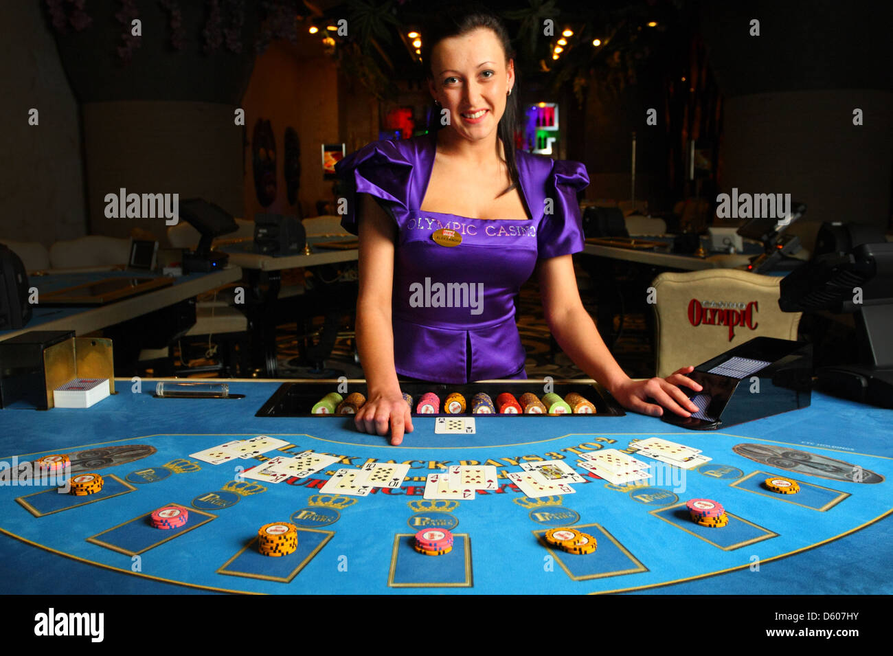 Smiling dealer, croupier showing cards in casino at blackjack table. Europe - Stock Image