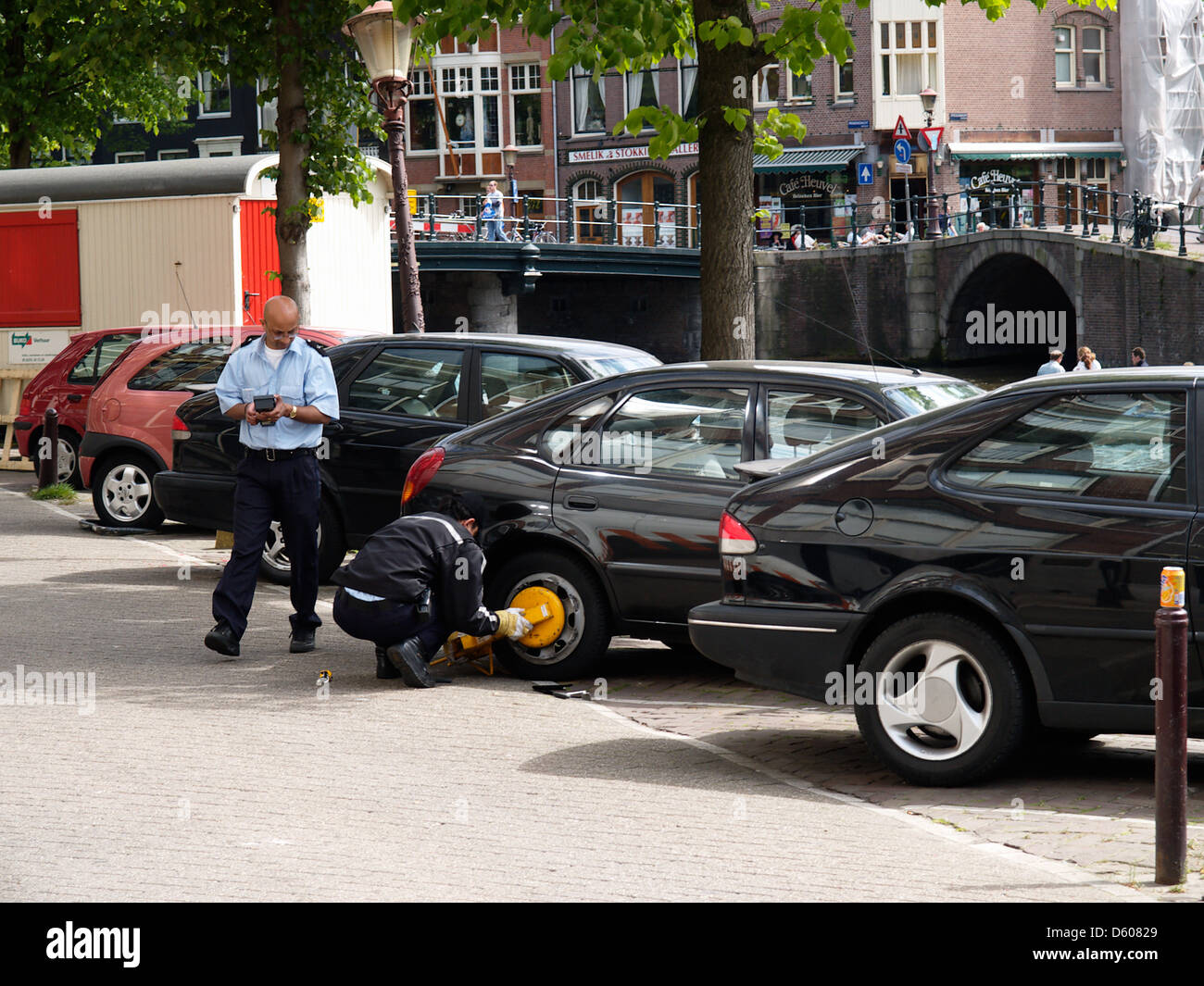 two parking attendants busy attaching a wheelclamp on the Prinsengracht canal, Amsterdam the Netherlands - Stock Image