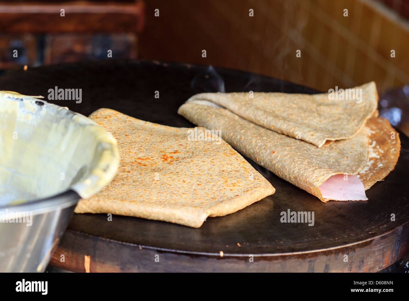 French savory crêpes on griddle with ham and cheese ready to go - Stock Image