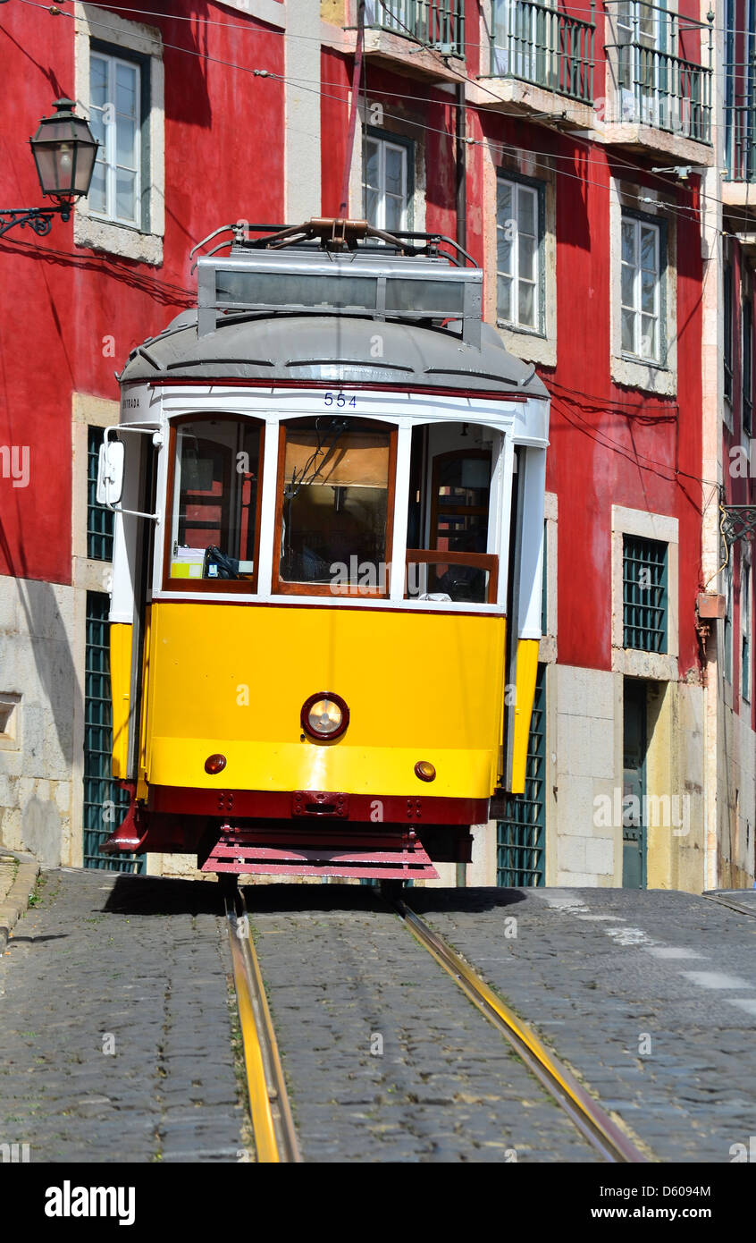 Yellow tram on narrow street, Alfama district of Lisbon. Portugal symbol - Stock Image