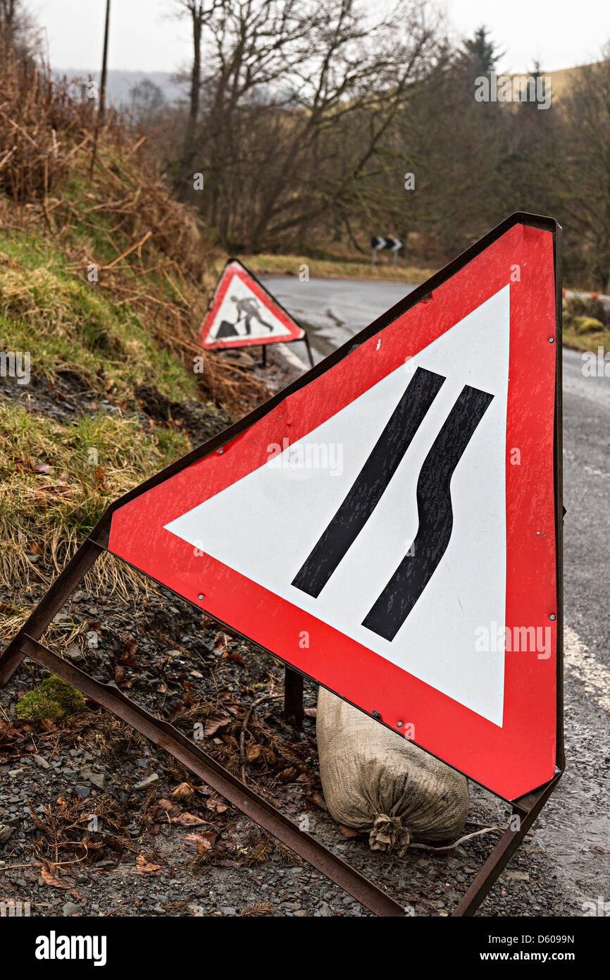Road signs for road narrows and roadworks near bend, Wales, UK - Stock Image