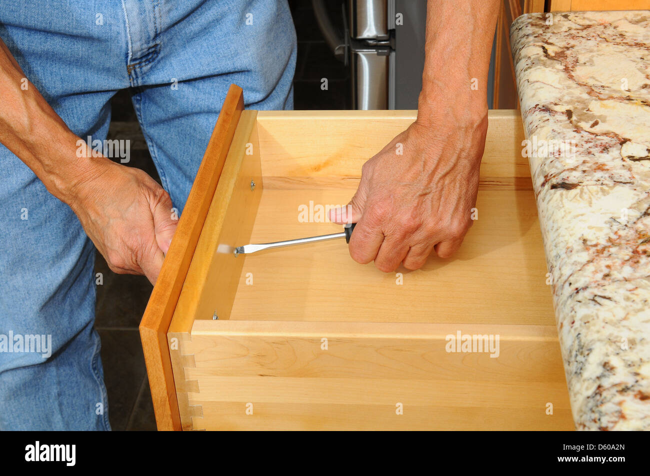 Closeup of a cabinet installer installing drawer hardware on ...