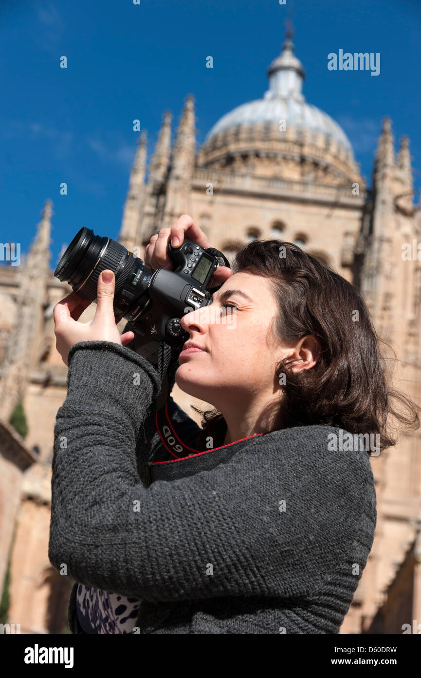 Tourist taking photos with Canon digital camera outside Salamanca New Cathedral, Spain - Stock Image