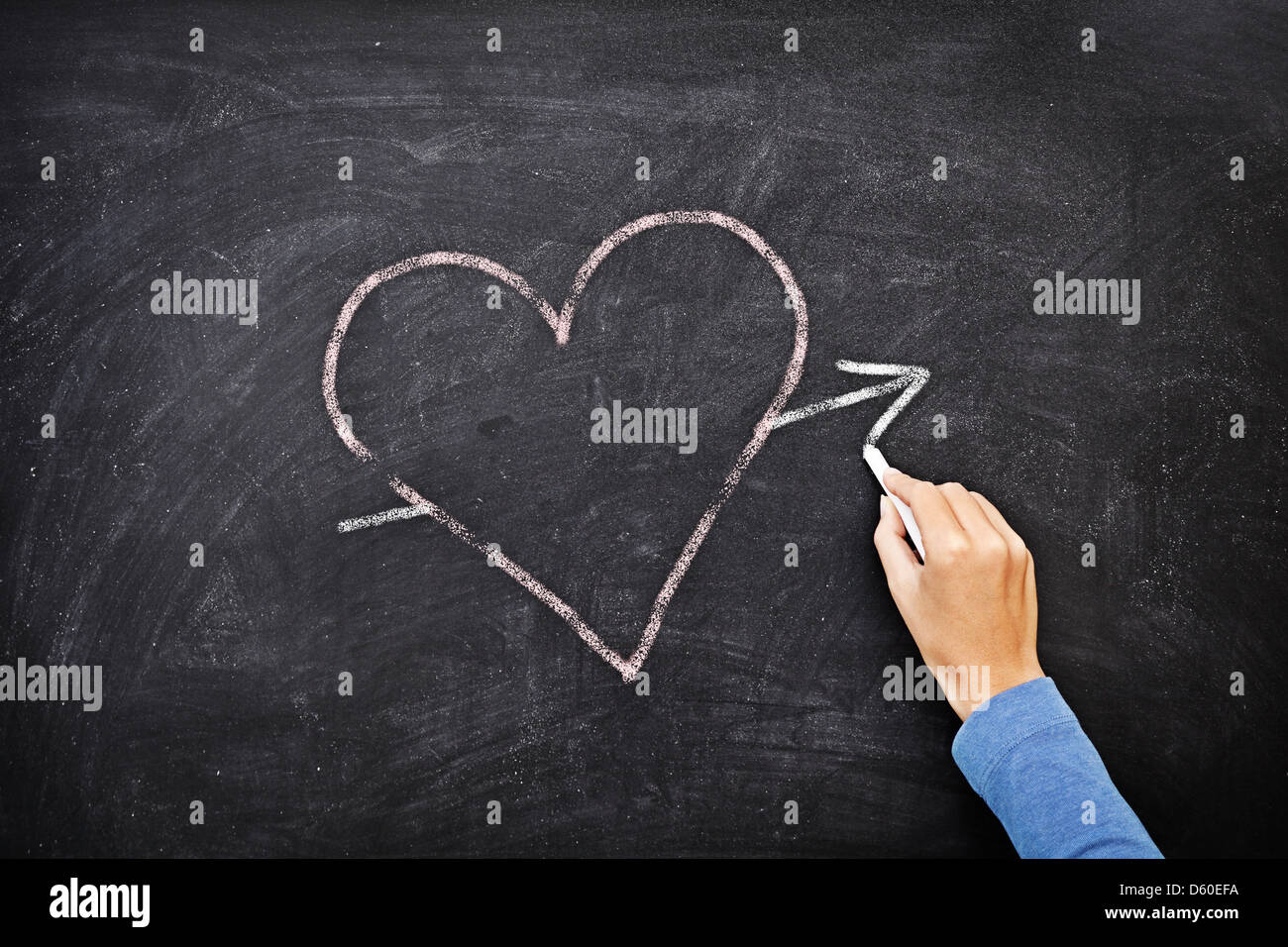 Hand drawing heart with chalk on chalkboard - love concept - Stock Image