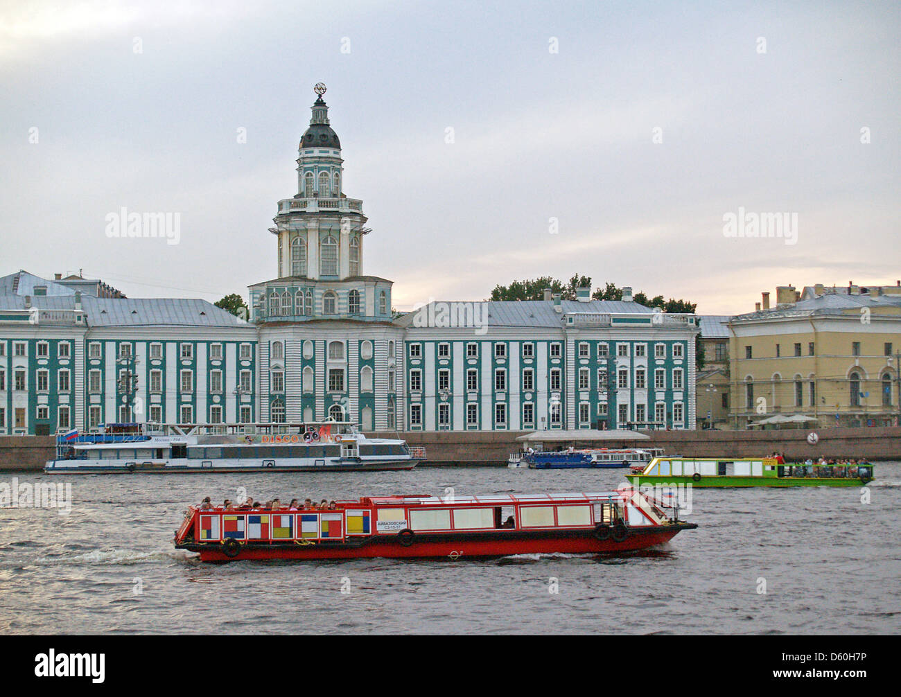 A canal boat cruising by Kunstkamera Museum on the Neva River,St.Petersburg - Stock Image
