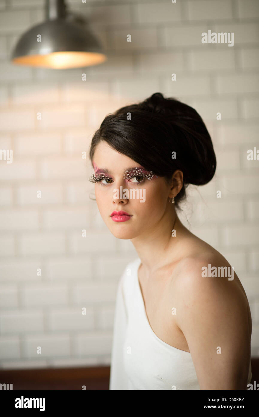 A beautiful young woman teenage girl with 1960's style hair, clothes and makeup, big