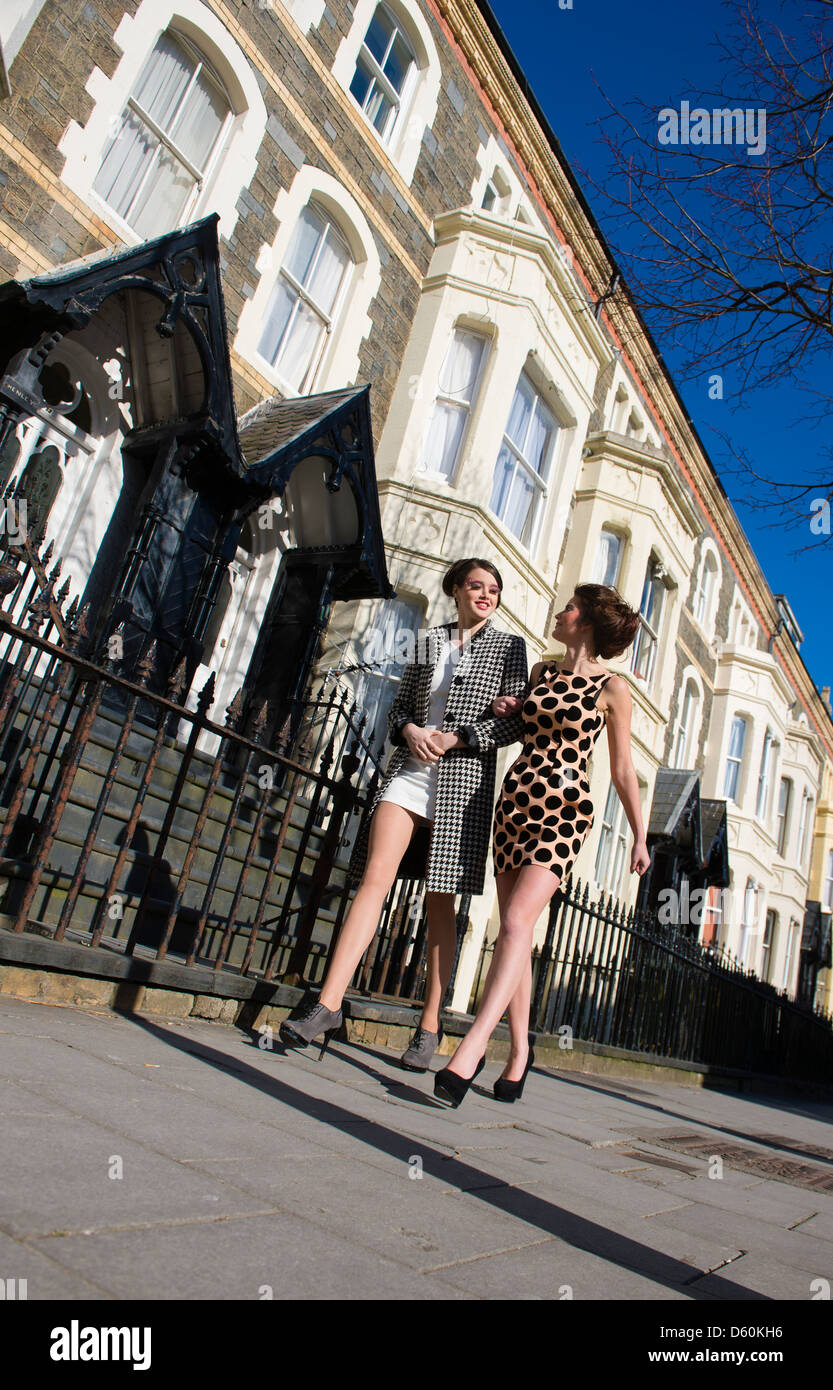 Two young woman with 1960's style hair makeup and clothes walking arm in arm on the street, sunny day, town - Stock Image