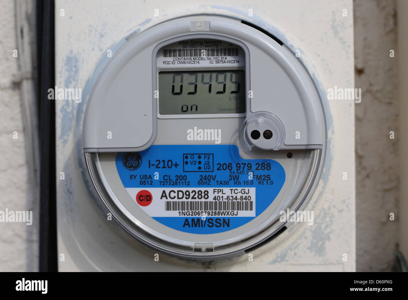 a new digital electric electricity power meter on the side of a house - Stock Image