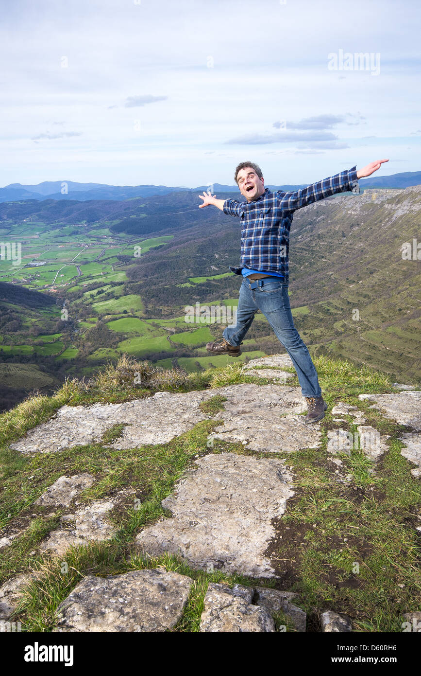 Male thirty something doing a very high star jump on mountain top - Stock Image