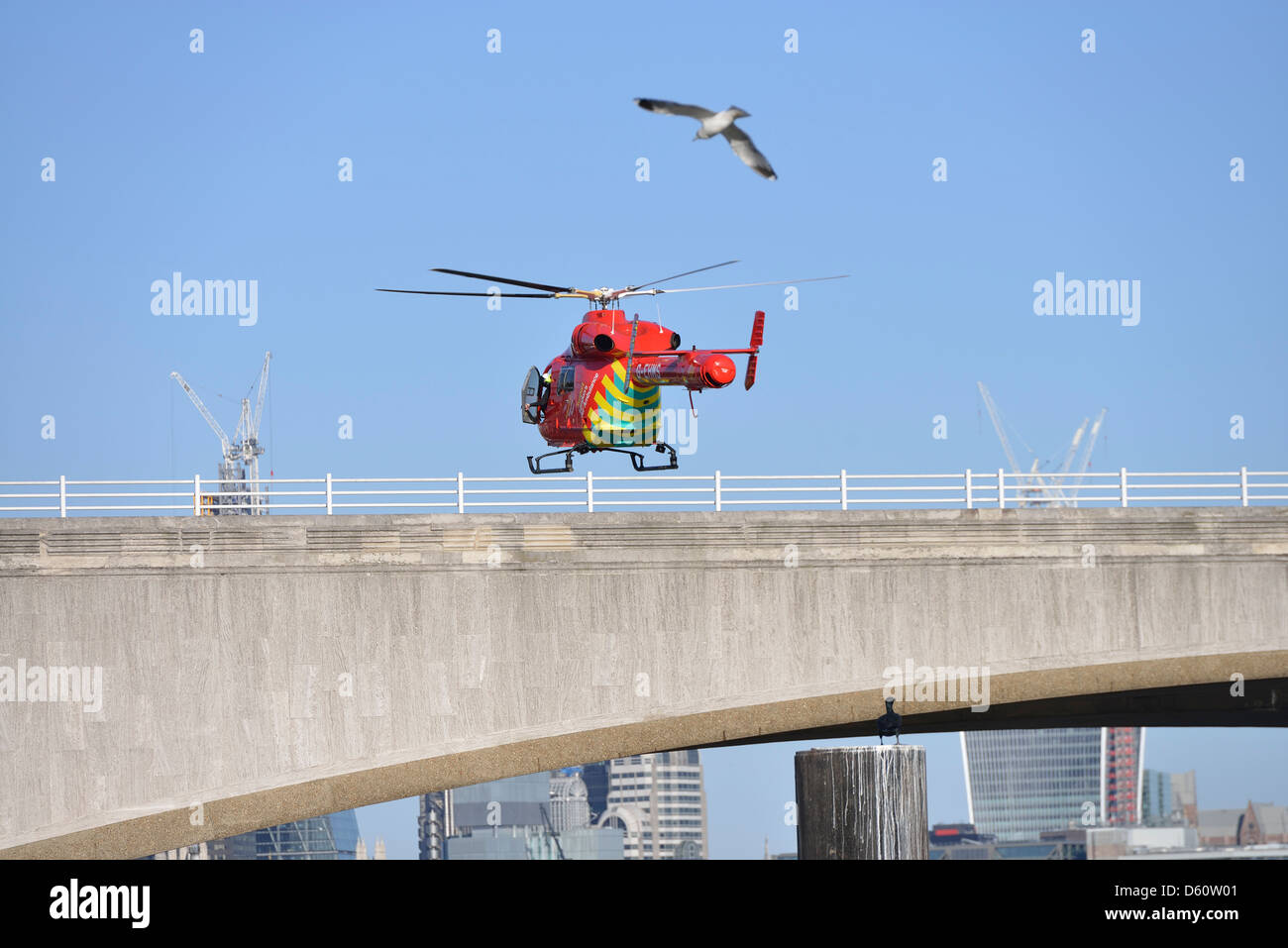 London, England - April 02, 2013: A London Air Ambulance helicopter lands at an emergency scene on Waterloo Bridge. - Stock Image