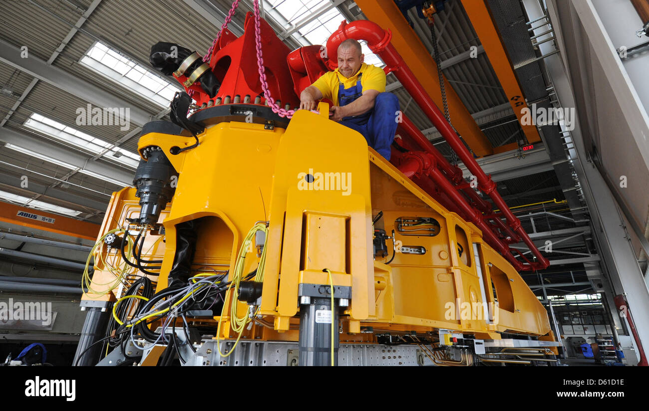 An employee of concrete pump manufacturer Putzmeister assembles a concrete pump in Aichtal, Germany, 17 April - Stock Image