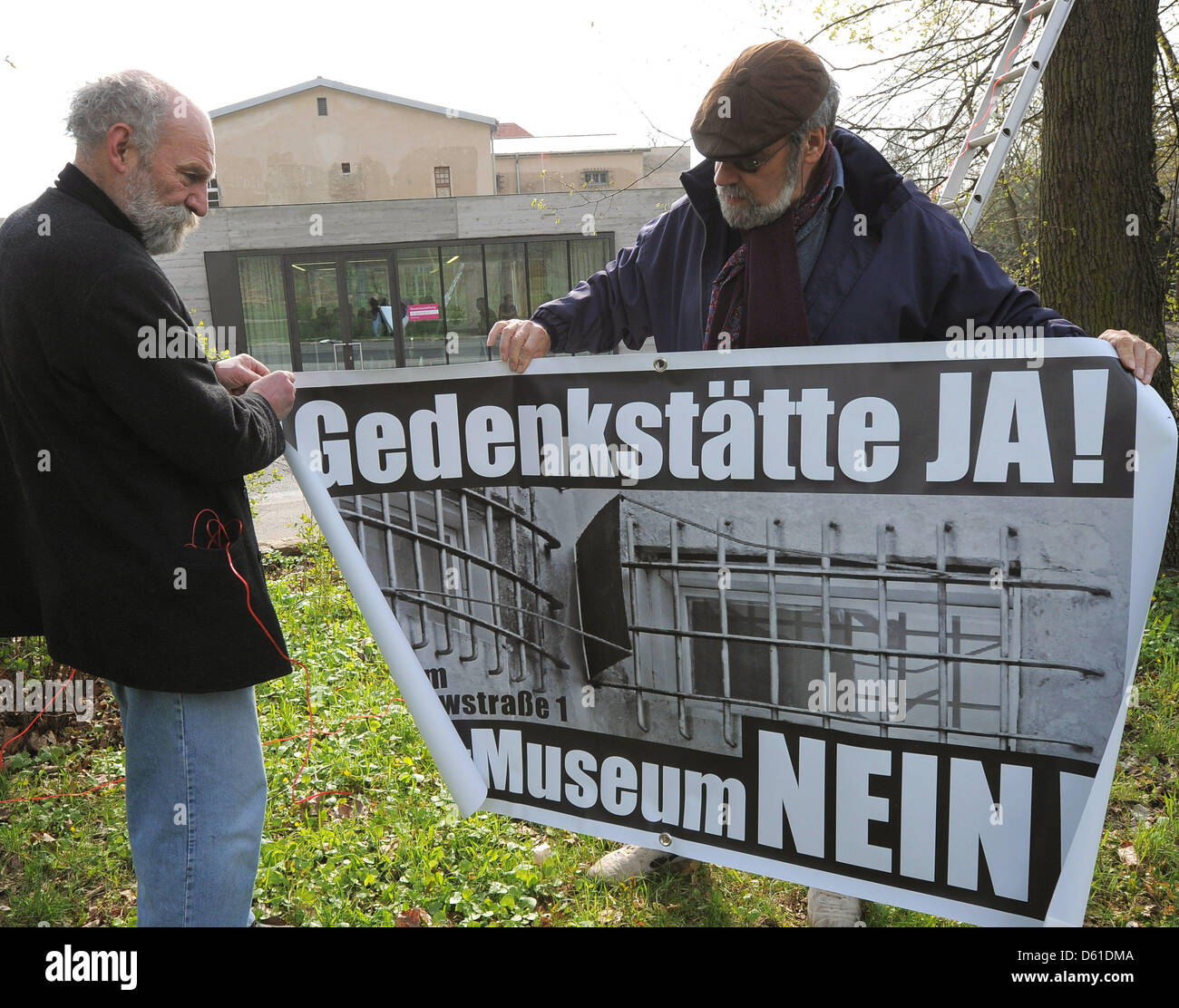 Dirk Jungnickel (L) and Bob Bahra put up a protest poster in front of the memorial site Leistikowstraße in - Stock Image