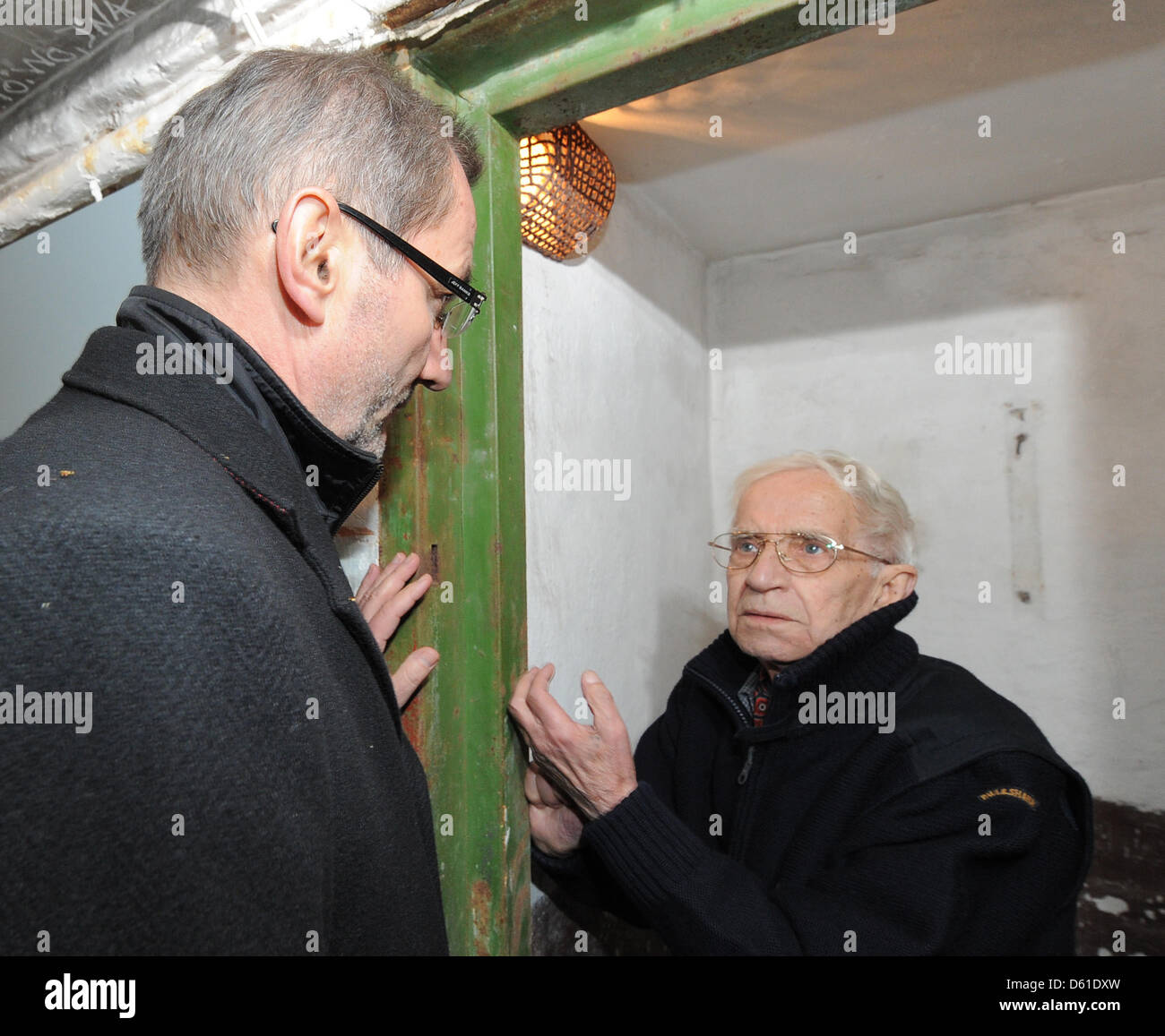Premier of Brandenburg Matthias Platzeck (L) stands with former prisoner Peter Seele in his cell in the basement - Stock Image