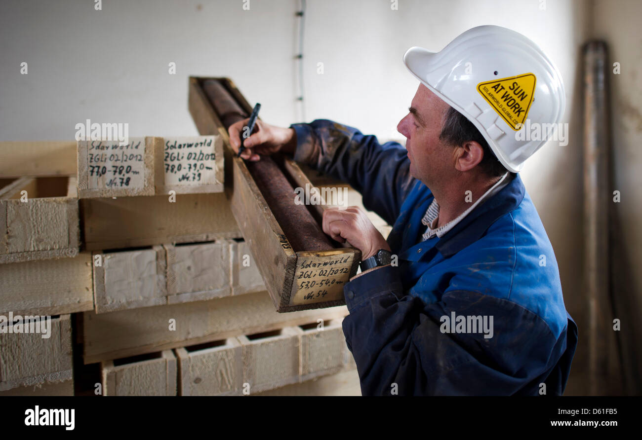 Drilling technician Volker Schmalfuss labels a core sample near a drilling rig during a survey for lithium for SolarWorld - Stock Image