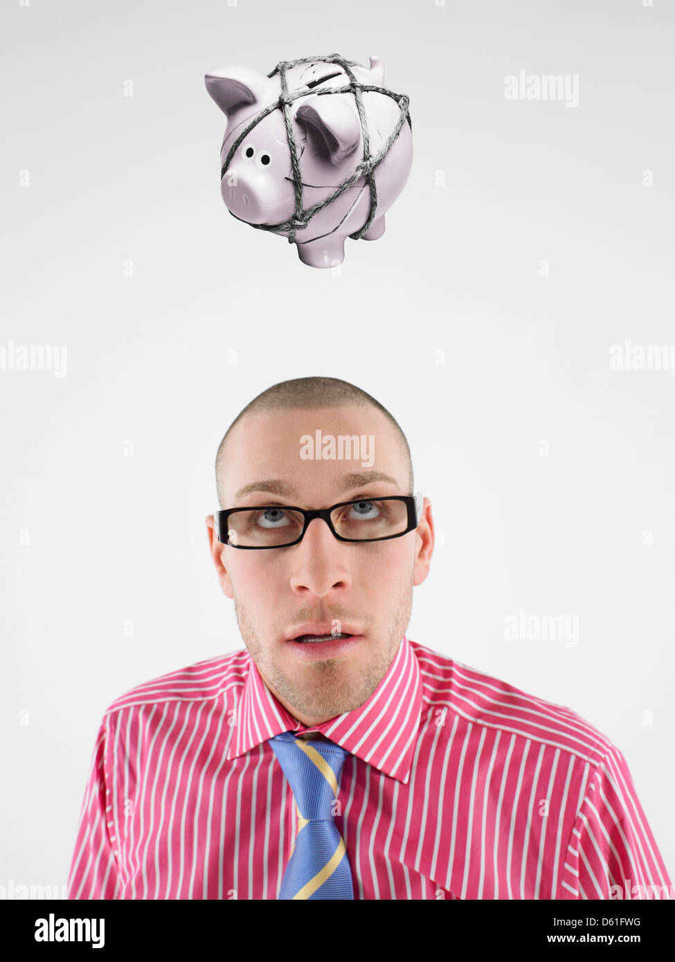 Young businessman looking up t piggy bank tied with rope representing trapped finances - Stock Image