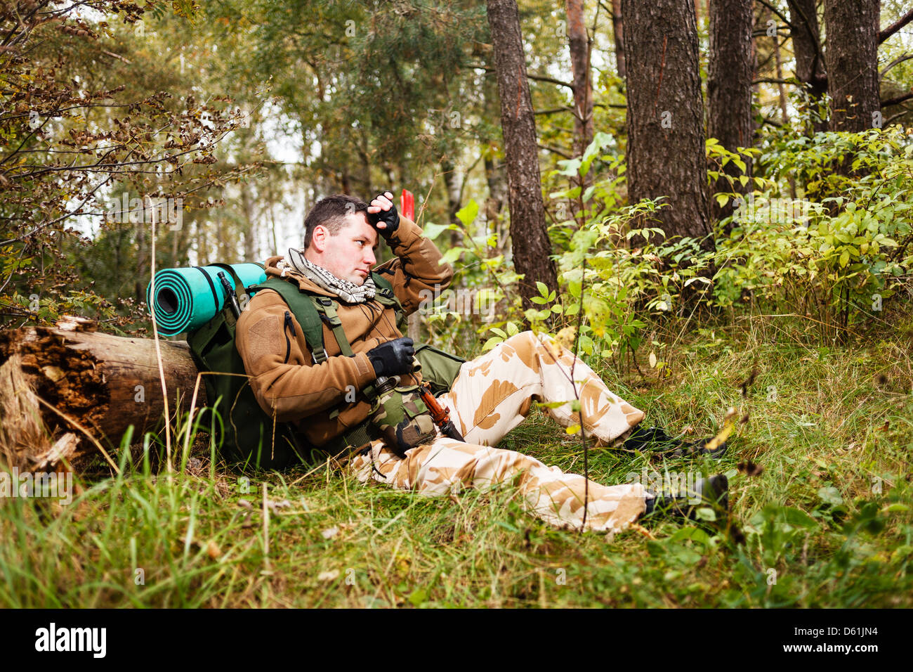 Soldier relaxing in a forest. - Stock Image